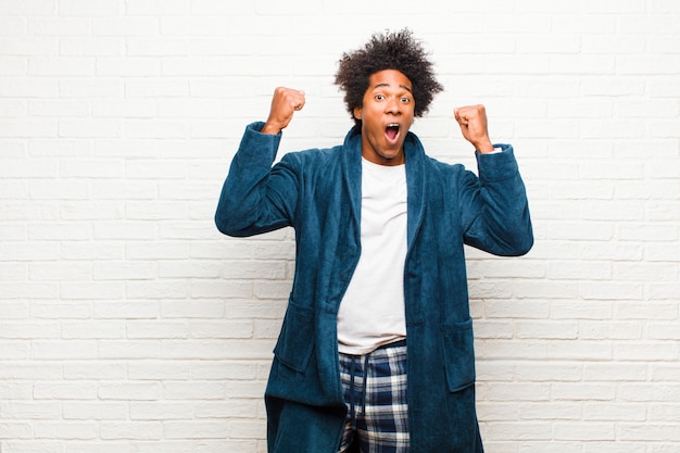 Young black man wearing pajamas with gown celebrating an unbelievable success like a winner, looking excited and happy saying take that! against brick wall