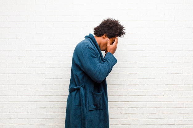 Young black man wearing pajamas with gown covering eyes with hands with a sad, frustrated look of despair, crying, side view against brick wall