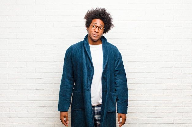 Young black man wearing pajamas with gown feeling confused and doubtful wondering or trying to choose or make a decision against brick wall