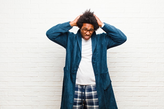 Young black man wearing pajamas with gown feeling frustrated and annoyed, sick and tired of failure, fed-up with dull, boring tasks against brick wall