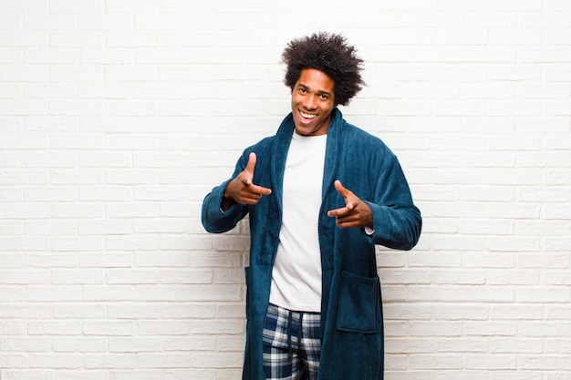 Young black man wearing pajamas with gown feeling happy, cool, satisfied, relaxed and successful, pointing , choosing you against brick wall