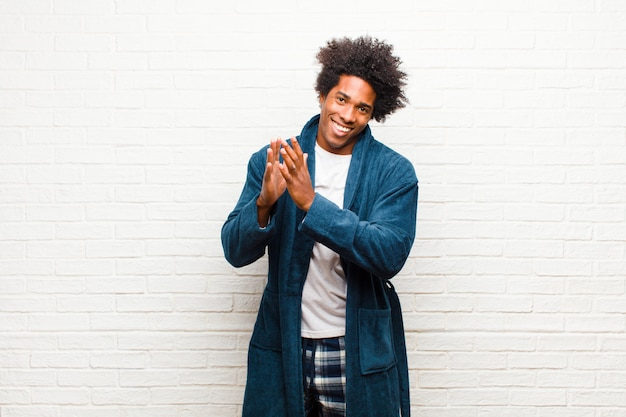 Young black man wearing pajamas with gown feeling happy and successful, smiling and clapping hands, saying congratulations with an applause against brick wall
