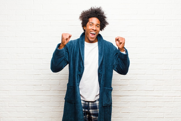 Young black man wearing pajamas with gown feeling happy, surprised and proud, shouting and celebrating success with a big smile on brick wall