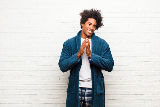 Young black man wearing pajamas with gown feeling proud mischievous and arrogant while scheming an evil plan or thinking of a trick against brick wall