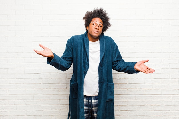 Young black man wearing pajamas with gown feeling puzzled and confused, unsure about the correct answer or decision, trying to make a choice