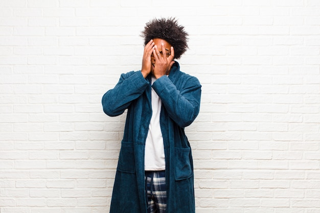 Young black man wearing pajamas with gown feeling scared or embarrassed, peeking or spying with eyes half-covered with hands against brick wall