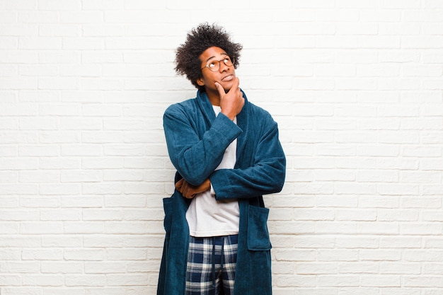 Young black man wearing pajamas with gown feeling thoughtful, wondering or imagining ideas, daydreaming and looking up to copy space