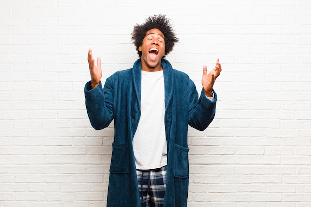 Young black man wearing pajamas with gown furiously screaming, feeling stressed and annoyed with hands up in the air saying why me