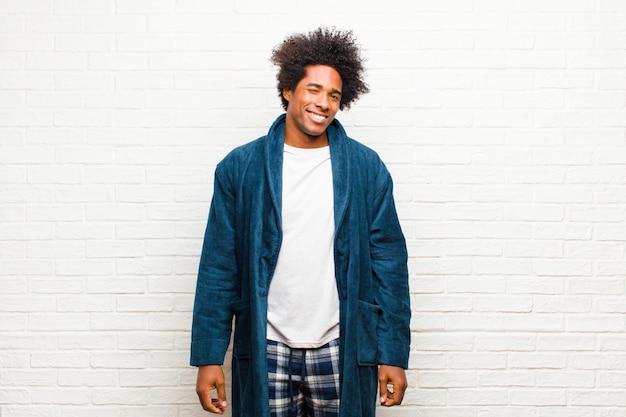 幸せでフレンドリーなガウンを着てパジャマを着ている若い黒人男性、笑顔でレンガの壁に前向きな態度で目をウインク