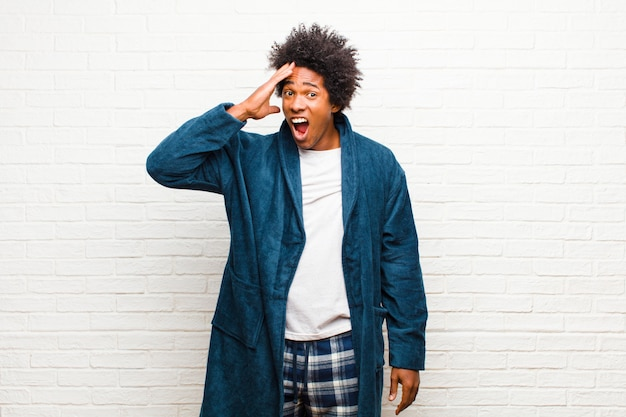 Young black man wearing pajamas with gown looking happy, astonished and surprised, smiling and realizing amazing and incredible good news against brick wall