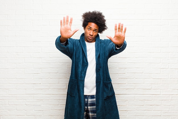 Young black man wearing pajamas with gown looking serious, unhappy, angry and displeased forbidding entry or saying stop with both open palms  brick wall