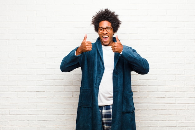 Young black man wearing pajamas with gown smiling broadly looking happy, positive, confident and successful, with both thumbs up