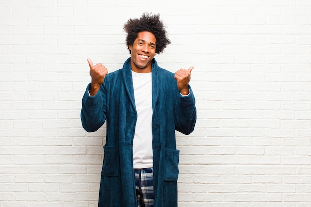 Young black man wearing pajamas with gown smiling joyfully and looking happy, feeling carefree and positive with both thumbs up against brick wall
