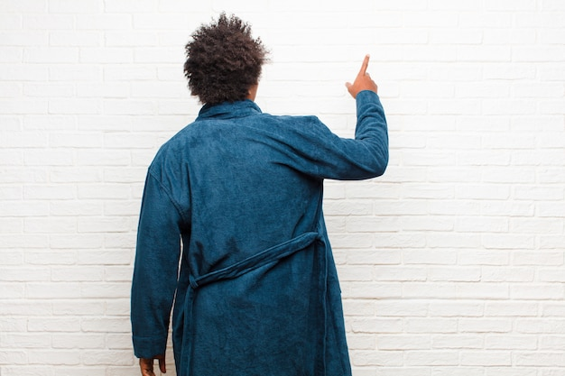 Young black man wearing pajamas with gown standing and pointing to object on copy space, rear view against brick wall