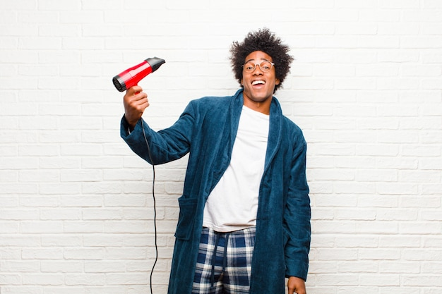 Young black man wearing pajamas with a hair dryer against brick