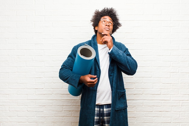 Young black man wearing pajamas  with a yoga mat