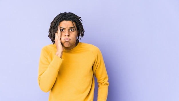 Young black man wearing rasta hairstyle blows cheeks, has tired expression. facial expression concept.