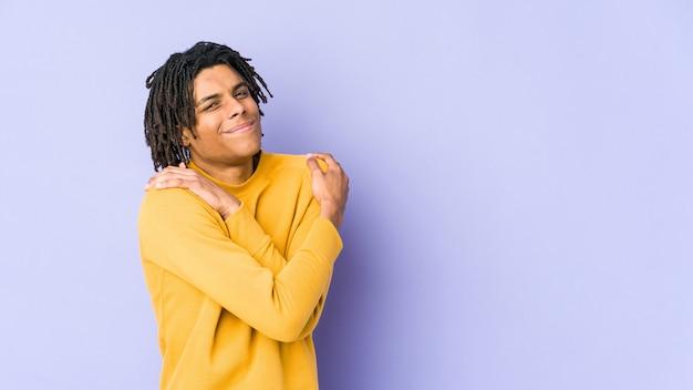 Rasta 헤어 스타일을 입고 젊은 흑인 남자는 평온하고 행복하게 웃고, 포옹.