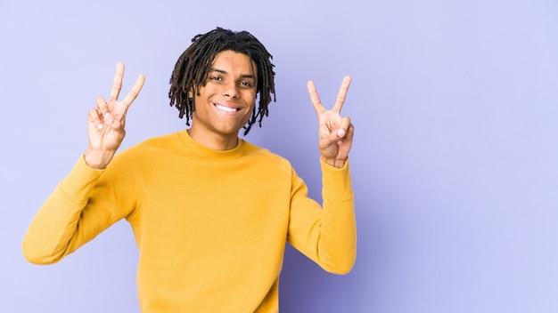 Молодой черный человек, носящий прическу раста, показывает знак победы и широко улыбается.