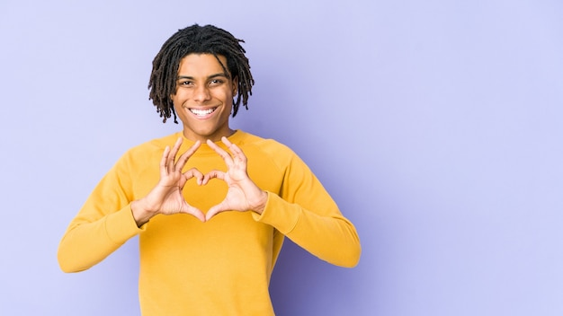 Young black man wearing rasta hairstyle smiling and showing a heart shape with hands.