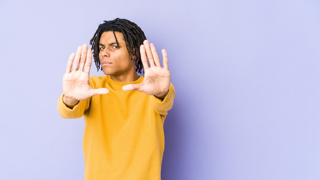 Young black man wearing rasta hairstyle standing with outstretched hand showing stop sign, preventing you.