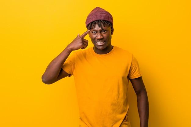 집게 손가락으로 실망 제스처를 보여주는 노란색 배경 위에 rastas를 입고 젊은 흑인 남자.