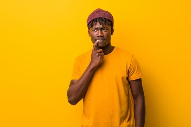 의심과 회의 식 옆으로보고 노란색 벽에 rastas를 입고 젊은 흑인 남자.