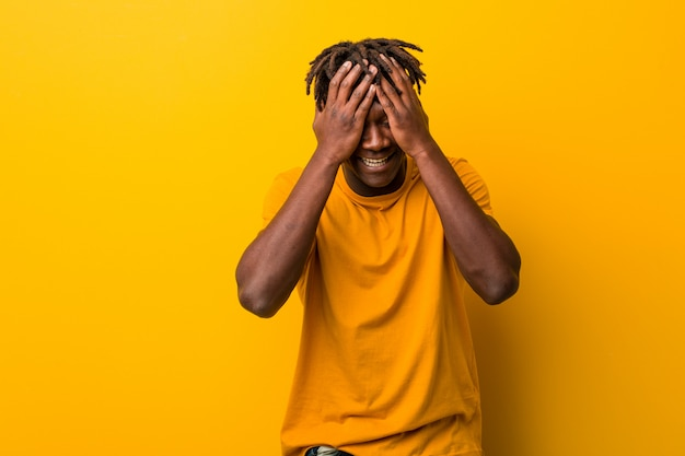 Young black man wearing rastas over yellow background covers eyes with hands