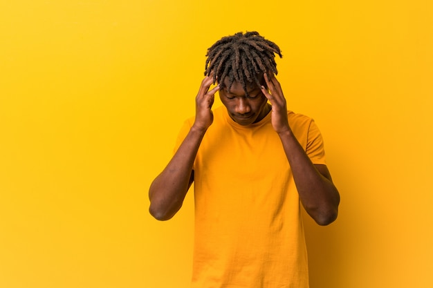 Young black man wearing rastas over yellow wall touching temples and having headache.