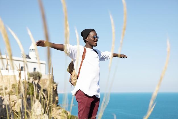 若い黒人男性が海を見下ろす岩の上に立って、腕を広げて、のんきで幸せで、笑顔で、新鮮な空気を呼吸している流行の流行に敏感な服を着ています。人、ライフスタイル、旅行