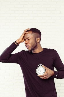 Young black man with alarm clock