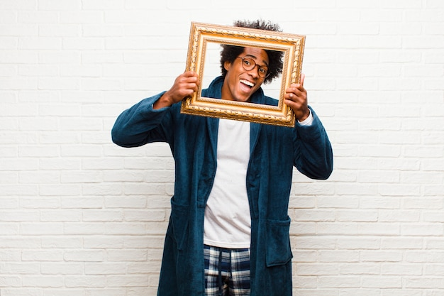 Young black man with a baroque frame at home