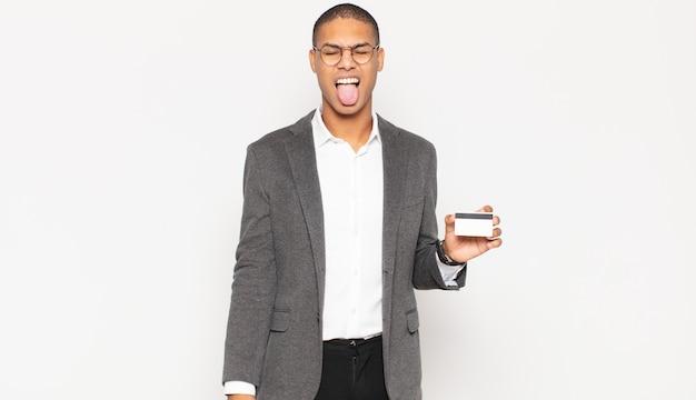 쾌활하고 평온하고 반항적 인 태도를 가진 젊은 흑인 남자, 농담하고 혀를 내밀고, 재미