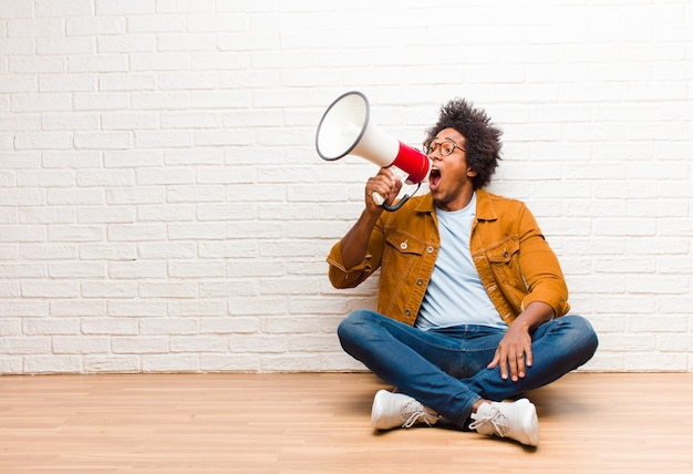 Young black man with a megaphone sitting on the floor