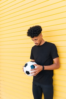 Young black man with soccer ball lowering head