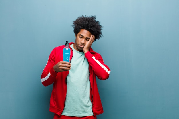 Young black man with a sport drink against blue grunge wall