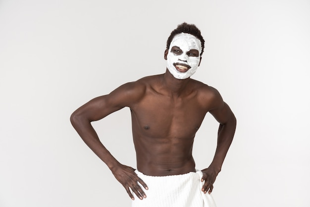 A young black man with a white bath towel around his waist going