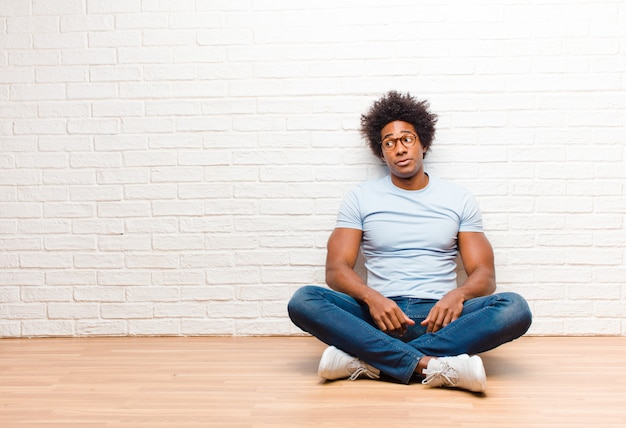 Young black man wondering, thinking happy thoughts and ideas, daydreaming, looking to blank space sitting on the floor at home