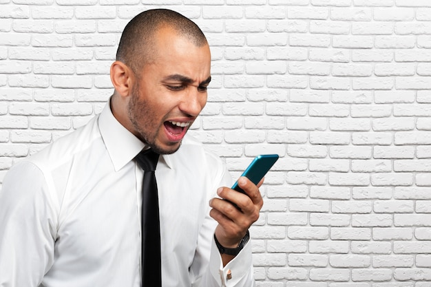 Young and black man yelling at the cellphone