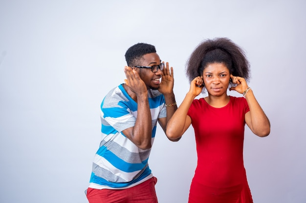 Young black man yelling at a lady who covers her ears with her finger