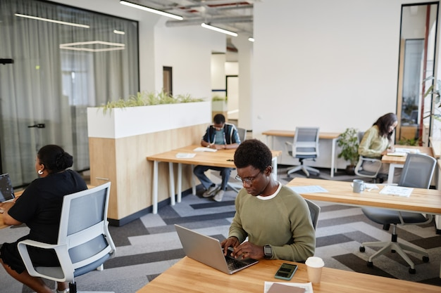Young black manager of marketing department working on laptop in open space office