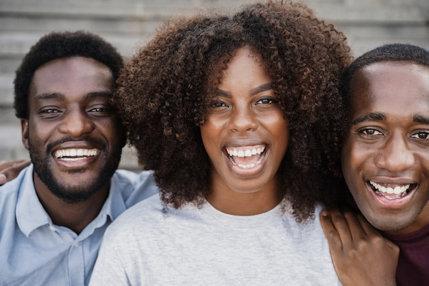 Young black people having fun looking at camera - main focus on african woman face