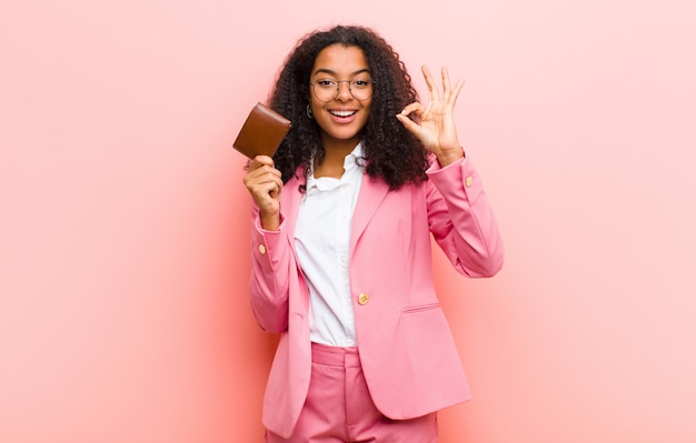 Young black pretty business woman with a wallet against pink wall