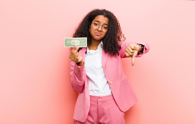 Young black pretty woman with dollar banknotes against pink wall