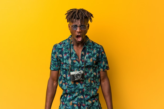 Young black rasta man wearing a vacation look screaming very angry and aggressive.