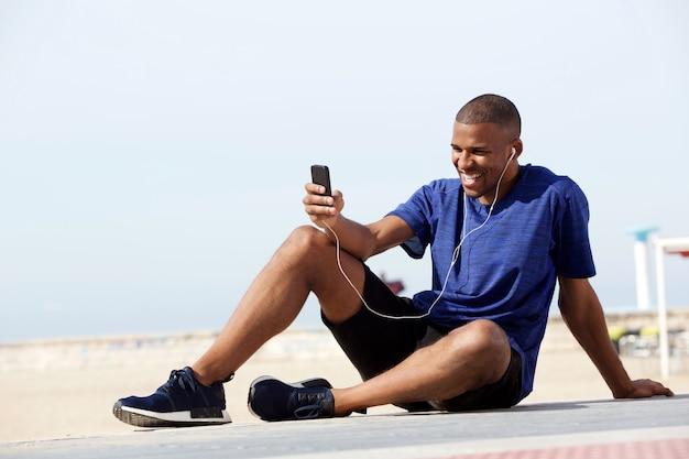 携帯電話とイヤホンで海辺でリラックスしている若い黒人