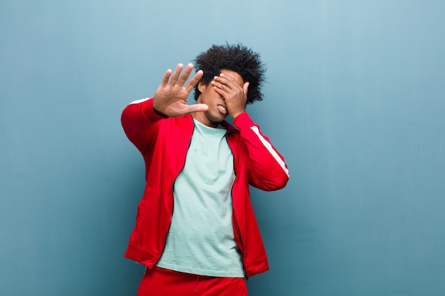 Young black sports man covering face with hand and putting other hand up front to stop camera, refusing photos or pictures against grunge wall