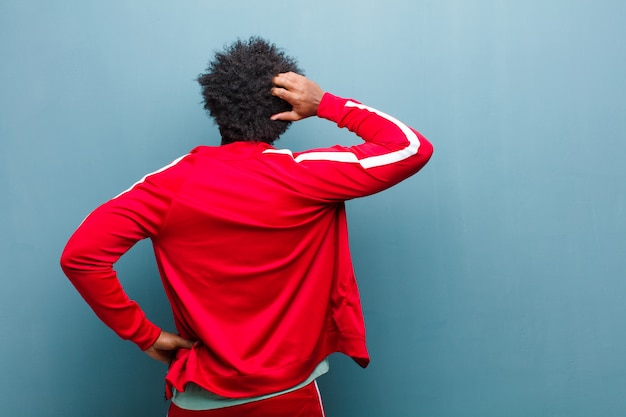 Young black sports man feeling clueless and confused, thinking a solution, with hand on hip and other on head, rear view against grunge wall