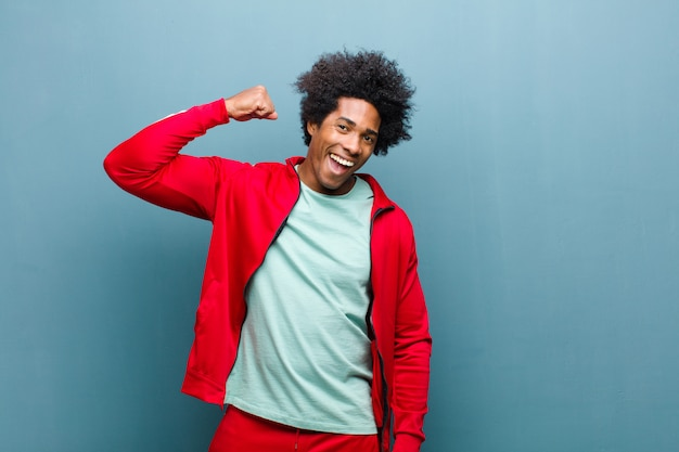 Young black sports man feeling happy, satisfied and powerful, flexing fit and muscular biceps, looking strong after the gym