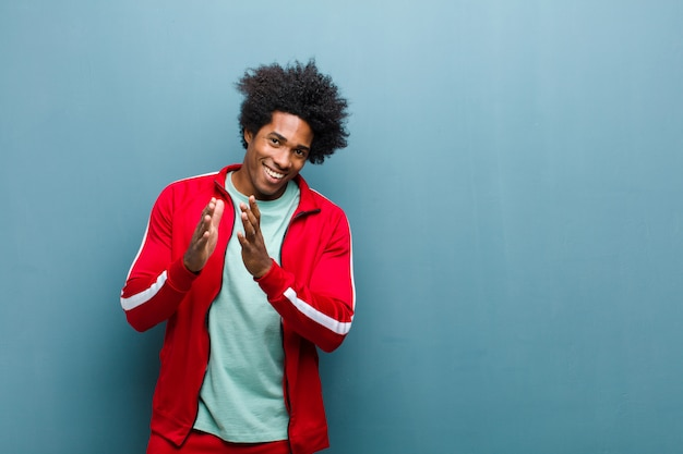 Young black sports man feeling happy and successful, smiling and clapping hands, saying congratulations with an applause on grunge wall